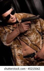 Athletic soldier in camouflage aiming with handgun
