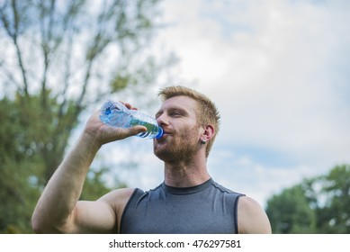Athletic sport man drinking water from a bottle
