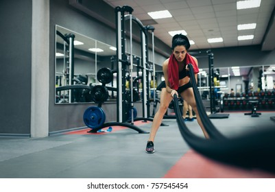 Athletic sportive young fit female working out in functional training gym doing crossfit exercise with battle ropes, copyspace for your text. Cross-fit workout motivation. People, sport concept.