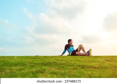 athletic sportsman resting after sport in the park and looking far away at the sunset