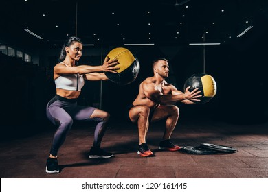 athletic sportsman and sportswoman doing squats with medicine balls together in dark gym