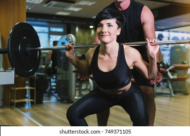 Athletic sportswoman squatting while lifting a barbell at gym while male trainer is supporting her