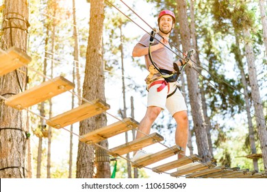 Athletic Sporty Guy Doing Activity in Adventure Park with all Climbing Equipment like Helmet, Rope and Carabiner. Active People Climb on the Trees and Having Fun Outdoors Enjoying Nature Landscape.