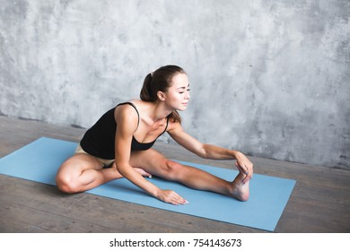 Athletic sporty woman doing yoga exercise stretching her leg at home.