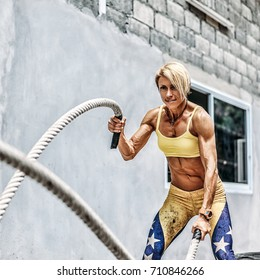 Athletic strong woman doing some exercises with a rope