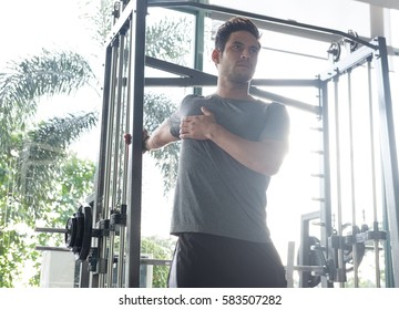 athletic team men stretching his chest and shoulder in the gym, fitness concept