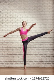 Athletic teen girl acrobat gets ready to perform high swing foot