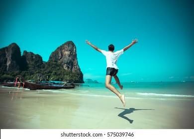 Athletic teenage boy enjoying the summer jumping in a tropical beach