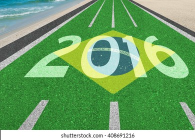 """Athletic track with Brazilian colors word 2016 and flag """"Order and Progress"""" in English leading to Rio de Janeiro Brazil and beach"""