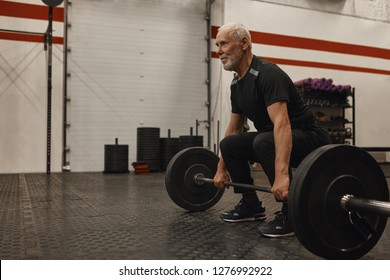 Athletic unshaven grandfather wearing stylish sports clohtes and sneakers posing at modern gym with powerlifting barbell, going to do deadlift, looking ahead of him with concentrated expression