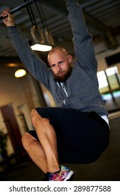 Athletic white man concentrating while doing pull ups with knees bent