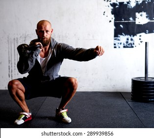 Athletic white man doing squats while lifting kettlebells
