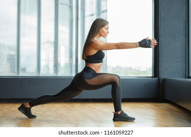 athletic woman in black sportswear doing lunges near window in gym