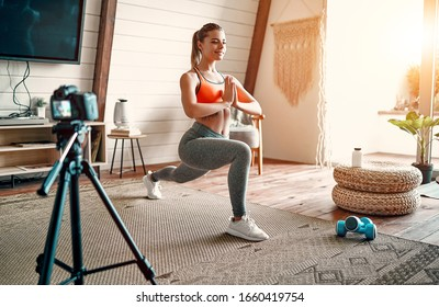 Athletic woman blogger in sportswear shoots video on camera as she does exercises at home in the living room. Sport and recreation concept. Healthy lifestyle.