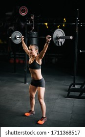 Athletic woman bodybuilder with perfect fitness body working out with barbell and lifts heavy barbell over her head. Concept of healthy lifestyle and workouts in a modern dark gym.