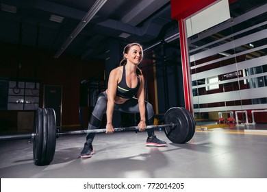 athletic woman doing deadlift with a barbell on a standing position, legs at shoulder level