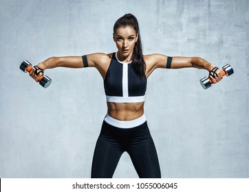 Athletic woman doing exercise for arms. Photo of muscular fitness model working out with dumbbells on grey background. Strength and motivation