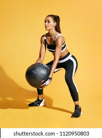 Athletic woman doing exercise with med ball. Photo of sporty latin woman in fashionable sportswear on yellow background. Strength and motivation.