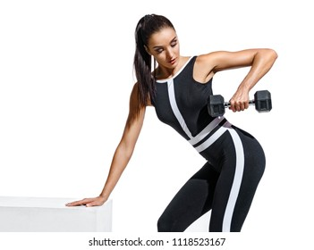 Athletic woman doing exercises with dumbbells for hands. Photo of fitness model in black sportswear isolated on white background. Strength and motivation