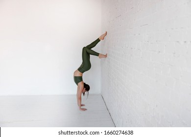 Athletic woman doing a handstand against the wall. Side view