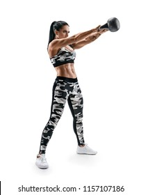 Athletic woman doing kettlebell swings. Photo of latin woman with good physique in fashionable sportswear isolated on white background. Strength and motivation. Full length