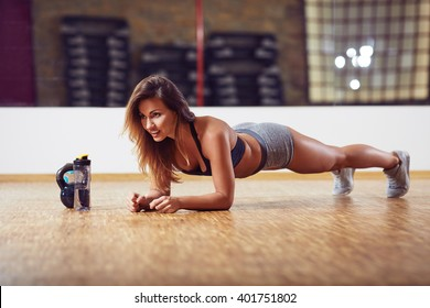 Athletic woman doing plank exercise at gym