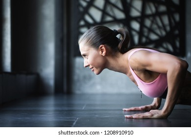 Athletic woman doing push-ups on the floor in a pink top. Yoga and working out.