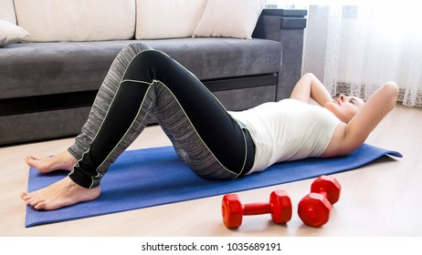 Athletic woman doing sit-ups on fitness mat at home