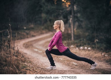 An athletic woman doing stretching exercises in forest.