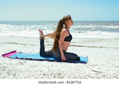 an athletic woman is doing yoga exercise on beach in Kapotasana or Pigeon Pose variation holding foot on an empty beach at the gulf of mexico in bonita springs florida with long hair blowing in wind