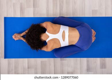 Athletic Woman Doing Yoga On Blue Fitness Mat Over The Hardwood Wood Floor