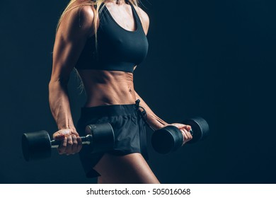 Athletic woman with dumbbells on a dark background