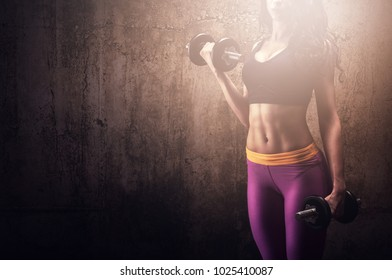 Athletic woman with dumbbells training in gym