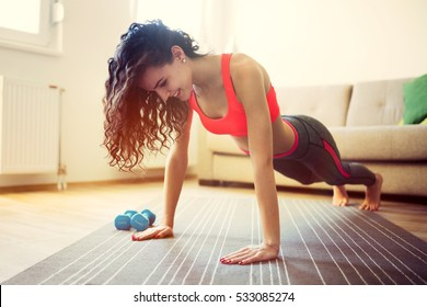 Athletic woman exercising at home doing pushups