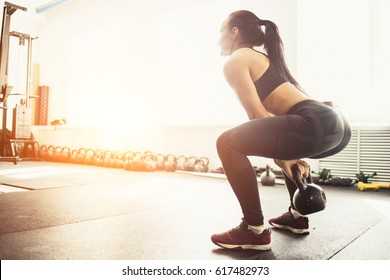 Athletic woman exercising with kettle bell while being in squat position. Muscular woman doing cross fit workout at gym.