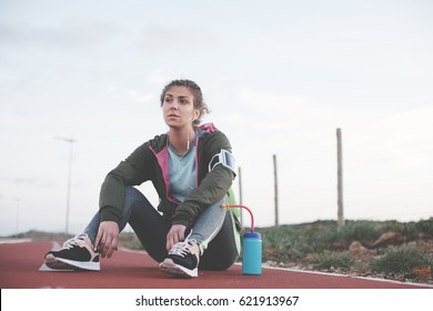 Athletic woman with flask sitting on the running track outdoors. Sport in nature near the field