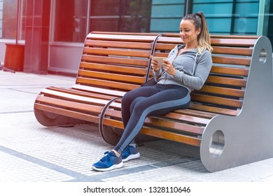 An athletic woman in a grey sweater and a black leggings sitting on a bench and using her smartphone.