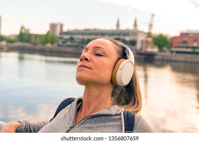An athletic woman in a grey sweater standing next to the bridge railing and listening to music on her headphones.
