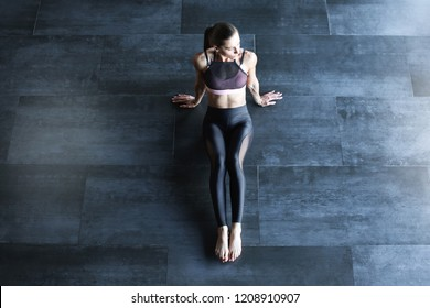 Athletic woman in a gym suit meditating on the floor top view with copy space for text. After workout.