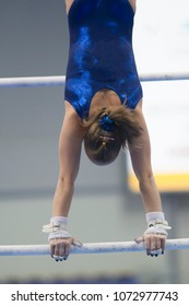 Athletic woman gymnasts performing exercises on the bar at the championship