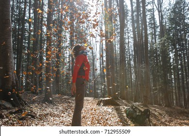 Athletic woman hiker enjoying the nature, throwing leaves in autumn sunny forest. Nature lover, active lifestyle, happiness and fun concept.