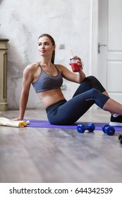 Athletic woman holding friut red detox smoothie after fitness workout. Fitness and healthy lifestyle concept with beautiful sportive caucasian model in the room.