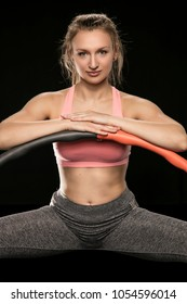 athletic woman holding hula hoop in her hands, isolated on the black background
