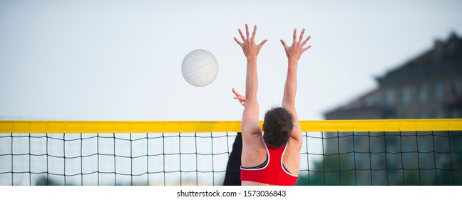 An athletic woman jumping to make wall block at beach volleyball net. Stretched arms and open hands to defend