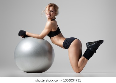 Athletic woman lies on a gym ball on gray background