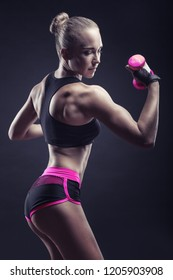 Athletic woman with pink dumbbells against a dark background. Side view