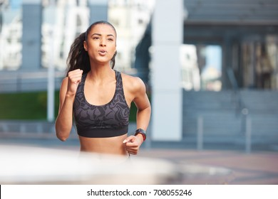 Athletic woman portrait with serious face running on the street in the City in front of the building with fitness tracker