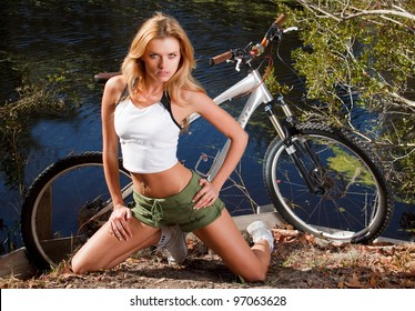 Athletic woman poses with mountain bike