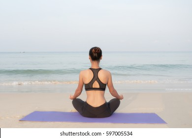 Athletic woman practicing yoga outdoor, on the Karon beach , Phuket , Thailand
