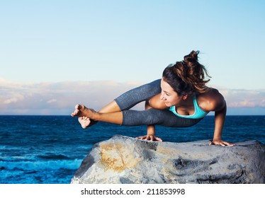 Athletic woman practicing yoga outdoors